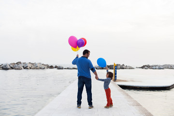 father and son looking at the horizon and holdings balloons