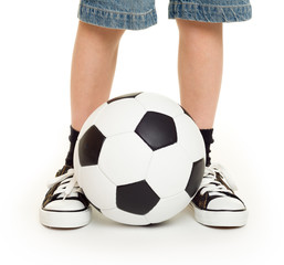 feet shod in sneakers and soccer ball