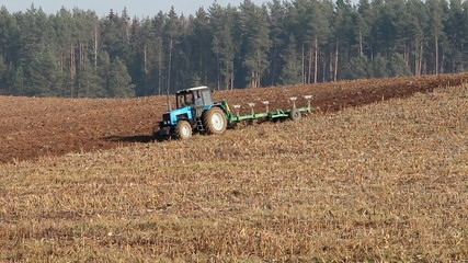 Tractor plowing field after harvesting corn