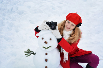 Girl and snow man, with camera on mountain, taking pictures