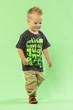 Cute little blond boy walking on green bacground
