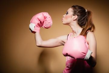 Female boxer wearing big fun pink gloves playing sports