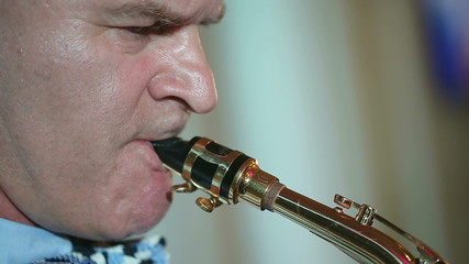 Middle-aged man playing a musical instrument saxophone.