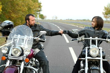 Two bikers on motorcycles handshaking with knuckle on road