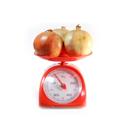 pomegranate on red weighing scale, isolate on white background