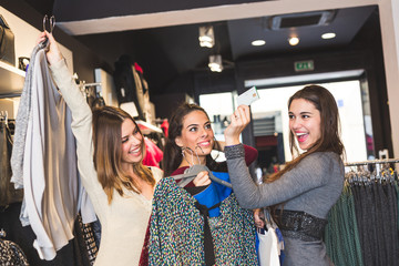 Happy Women with Credit Card in a Clothing Store