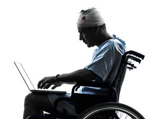 injured man in wheelchair computing laptop computer silhouette