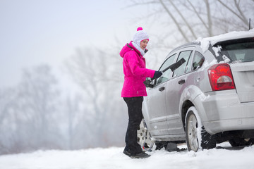 Woman cleaning snow from her car