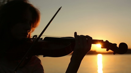 Girl violinist playing the violin at sunset on the lake.