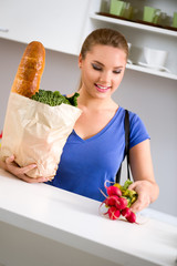 Young woman with groceries in shopping bag