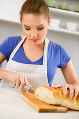 Woman in kitchen cutting bread
