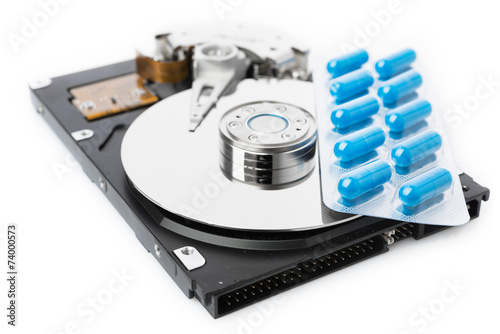 Pills on computer hard drive - concept technology background - 74000573
