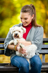 Smiling girl  holding cute maltese dog