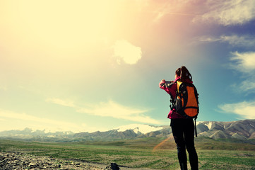 young woman tourist taking photo with smart phone in tibet
