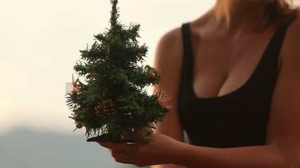 girl corrects small green christmas tree in her hands at  sunset