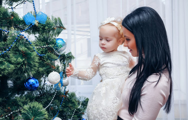 Happy mother and baby near Christmas tree