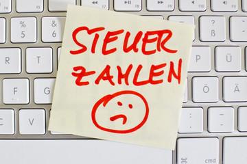 Notiz auf Computer Tastatur: Steuer zahlen