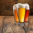 Different beer in glasses on wood