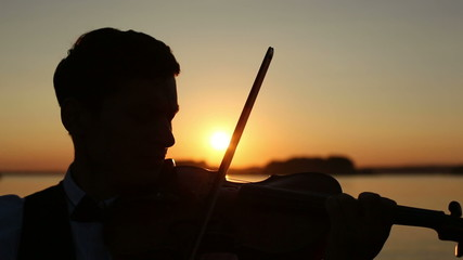 Violinist man play violin on nature at the sunset