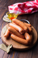 Tasty sausages on wooden board
