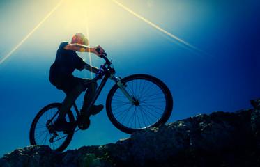 male cyclist on a mountain bike, backlit