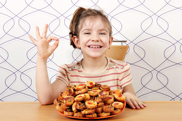 happy little girl with bruschetti and ok hand sign