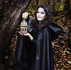 Beautiful witch with lantern in the forest