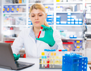 A woman laboratory assistant uses a computer research blood samp