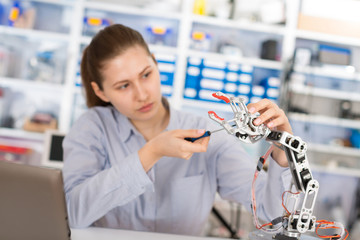 schoolgirl adjusts the robot arm model