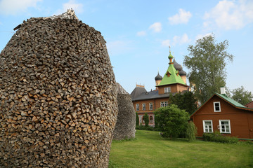 Brennholzstapel vor Klosterkulisse