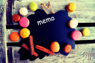 Colorful macaroons with chalk board on a wooden background