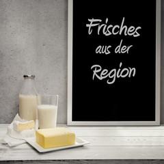 Butter, Milch und Camembert auf dem Sideboard mit Schreibtafel