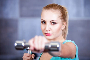 Strong blonde woman weightlifting at the gym