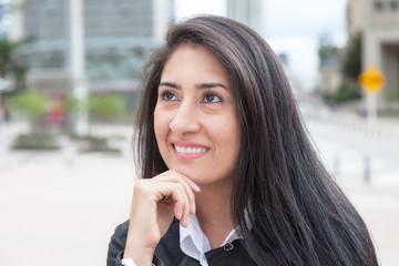 Träumende Frau mit langen schwarzen Haaren in der Stadt