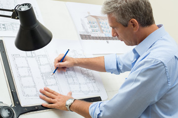 Architect Working At Drawing Table