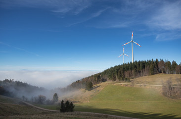 wind power mills above fog in black forest, Germany