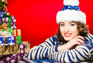 cheerful brunet portrait with holiday gifts on a red backgrond
