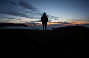 silhouetted man standing in sunset above valley