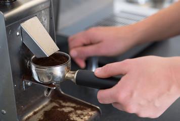 Barista with piston/portafilter grinding espresso beans.