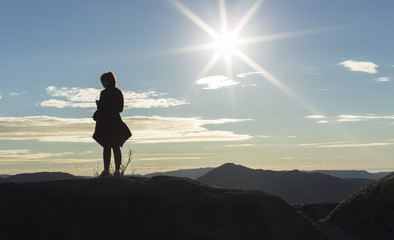 Silhouette woman listening to her music on a mountain