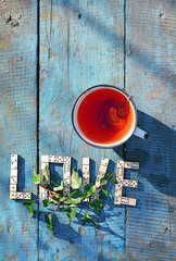 word love ??of wooden dominoes with cup tea