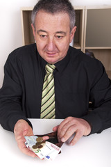 Businessman showing the meager contents of his wallet