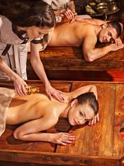 Couple having Ayurvedic spa treatment.