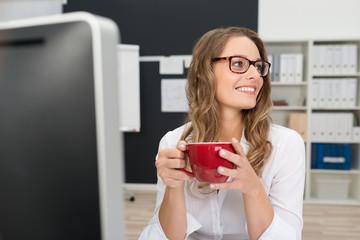 frau mit roter kaffeetasse am arbeitsplatz