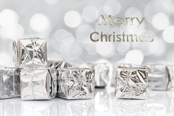 Merry Christmas gifts in shiny paper, bokeh lights background