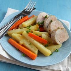 Sliced roast pork tenderloin with potatoes and carrots