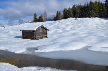 old wooden hut on snowy alpine meadow
