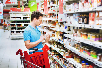 man reading label on the bottle in supermarket