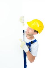 junger handwerker zeigt auf hinweisschild