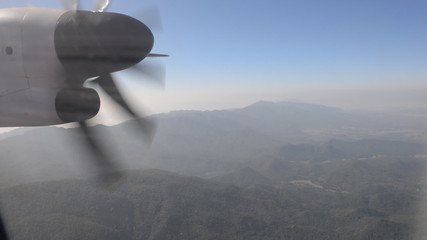 Turboprop airplane flying over mountain